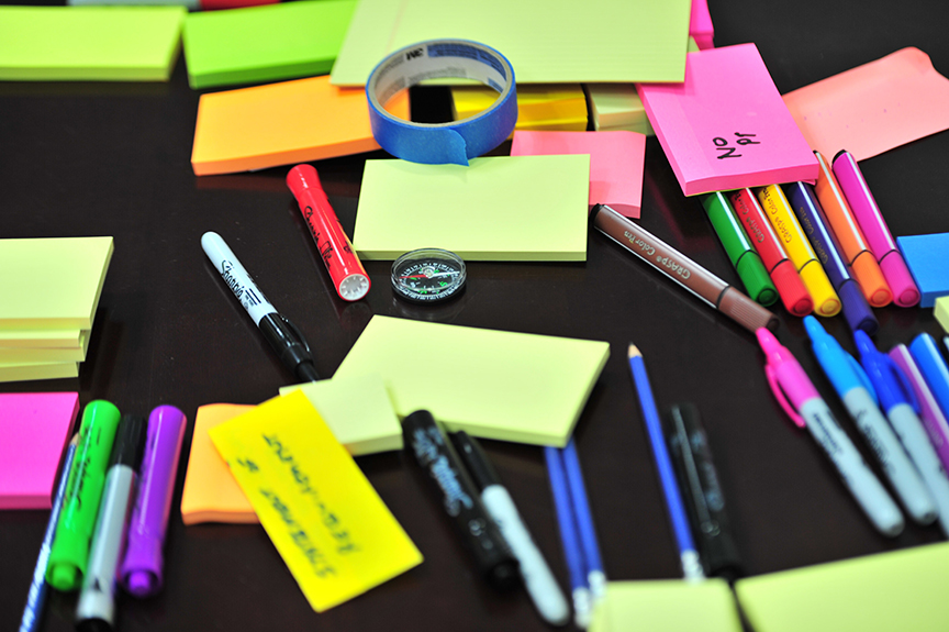 desk full of post-it notes and markers